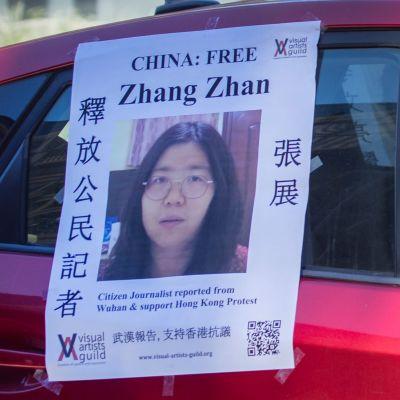 Två personer i munskydd sitter i en röd bil. På bilen hänger en lapp med en bild på journalisten Zhang Zhan och en uppmanan att fria henne från fängelset.