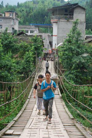 En man och en kvinna med korgar på ryggen går på en gångbro.