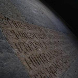 Kiveen hakattua kirjoitusta hämärässä valossa