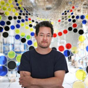 Jacob Hashimoto, en artist står med armarna i kors framför ett konstverk med färggranna cirklar.