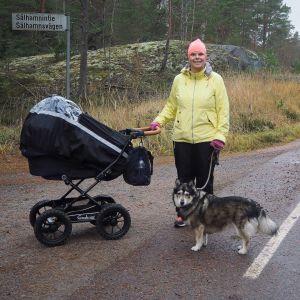 En kvinna med gul jacka och rosa mössa på promenad med barnvagn och hund.