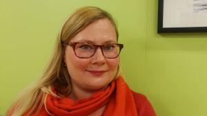 En kvinna med långt blont hår och glasögon står framför en limegrön vägg.