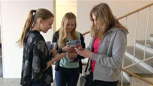 Flickor knapprar på telefonen i Åshöjdens skola i Helsingfors.