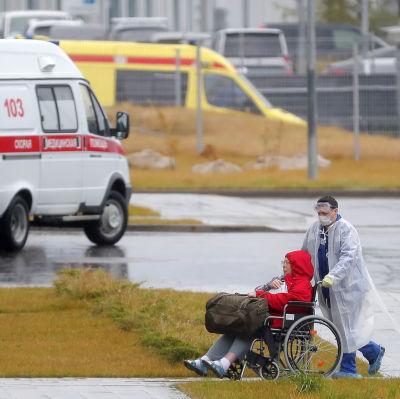 En sjukvårdare i skyddsdräkt rullar in en patient till ett sjukhusavdelning för covid-19-patienter i Moskva.