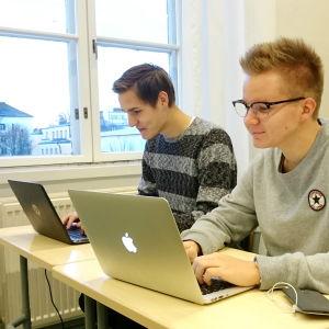Två skolelever jobbar vid sina datorer under en lektion.