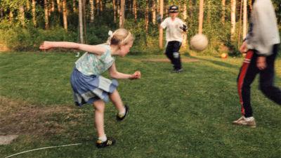 Lina som barn när hon spelar fotboll med sina bröder på en sommaräng. Hon har precis sparkat iväg fotbollen.