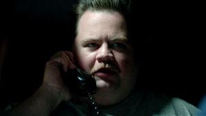 Närbild på Richard Jewell (Paul Walter Hauser) då han sitter i ett mörkt rum och håller i en telefonlur.