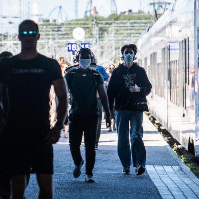 Ihmisiä saapuu junasta Helsingin rautatieasemalle.