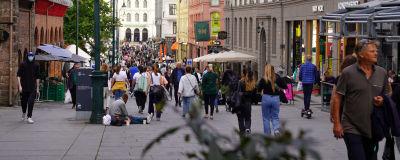En man sitter och tigger på en gata fylld av folk.