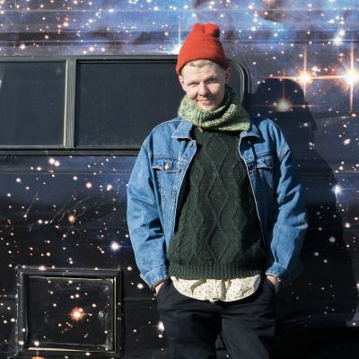 """Toimittaja Jussi Nygren matkailuauto """"Kosmobiilin"""" edessä. Matkailuauto on päällystetty kalvolla, johon on painettu Linnunrata."""