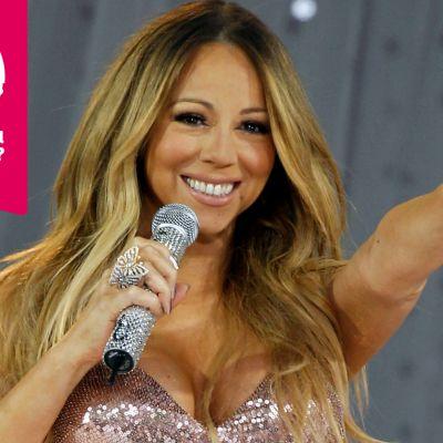 Mariah Carey ler brett, håller en mikrofon i ena handen och sträcker andra armen rakt ut framför sig..