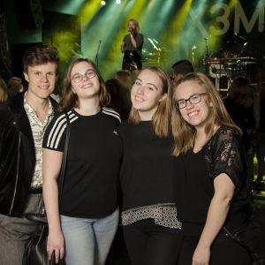 En kille och tre tjejer ler. De står framför en scen. Folk i bakgrunden.