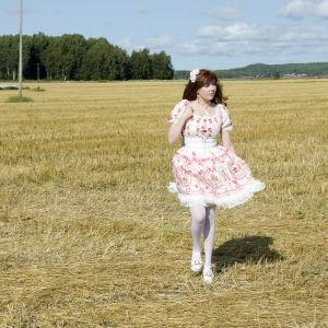 En kvinna klädd i så kallade Lolitakläder - en fluffig vit och rosa klänning med spetsar på. Hon har vita högklackade skor och blommor i håret. Hon går på en nyklippt åker.