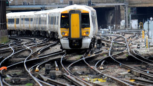 Brittiskt tåg anländer till en järnvägsstation i London.