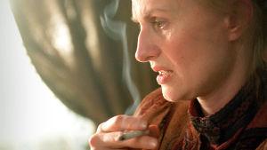 Sara Paavolaisen näyttelemä Venny Soldan kuvassa sivuttain. Hän piti sormiensa välissä palavaa tupakkaa.