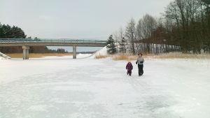 Två personer springer på isen under bron till Hyppeis i Houtskär