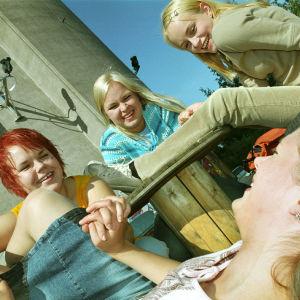 Sarjasta Hurja joukko. Neljä tyttöä nauraa. Yksi heistä on kaatunut maahan ja kolme nauraa hänen ympärillään.