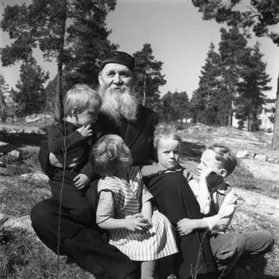 Kirjailija Frans Emil Sillanpää istuu kalliolla lasten kera.