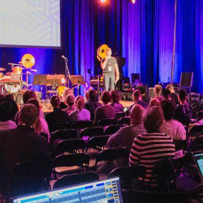 Publik och talare på en musikkonferens i en studio.
