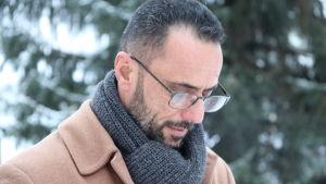En man i brun rock, grå halsduk och glasögon tittar ner i marken.