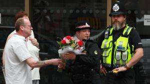 Poliser som står vakt nära attentatsplatsen får en blombukett.