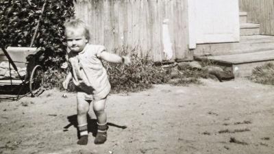En svartvit bild på Stina som barn. Hon har en bestämd min och springer på gården framför en träbyggnad.