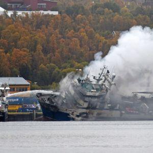 Rykande farttyg med slagsida i hamn under pågående släckningsarbete.