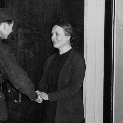 Matti Alanko lähdössä sotaan kotoaan taiteilijakoti Lallukasta, Apollonkatu 13. Martta-äiti hyvästelee poikaansa kotiovella.