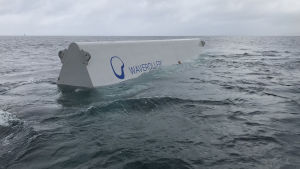 Ett vitt avlångt vattenkraftverk i metall i havet.