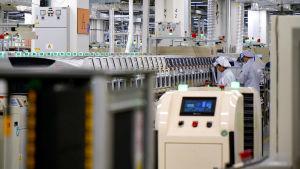 En rad med maskiner i en fabrik. Borta till höger står två anställda.