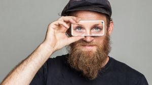 En man håller en telefon framför sina ögon, och hans ögon är ersatta av kvinnoögon.