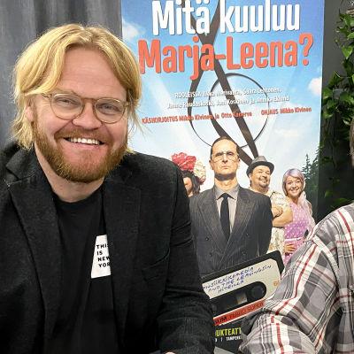 Otto Kanerva ja Mikko Kivinen hymyilevät kameralle. Heidän takanaan roll-up-juliste Mitä kuuluu Marja-Leena? -näytelmästä.