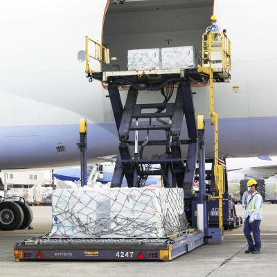 Lentokentän työntekijät purkavat rahtikonetta.