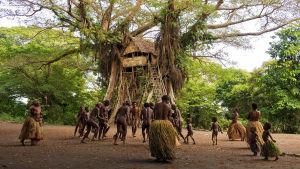 Människor som dansar på en stor öppen plats med ett trähus i bakgrunden