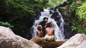 Selin (Marceline Rofit) och Wawa (Marie Wawa) sitter på en trädstam och ser på ett vattenfall.