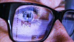 Lähikuvassa silmä, silmälasin linssi, johon heijastuu tekstiä näyttöpäätteeltä