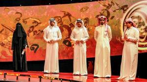 Hissa Hilal i svart tillsammans med andra manliga deltagare klädda i vitt i tv-programmet Millions Poet.