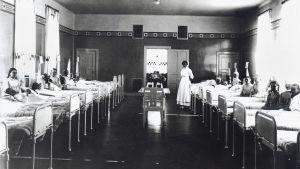 Kvinnor som ligger i sina sängar i en sjukhussal år 1910