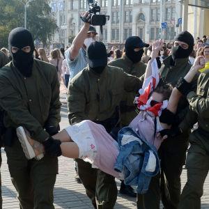 Män från säkerhetsstyrkorna, iklädda svarta huvor, bär bort en kvinnlig demonstrant under en demonstration i Minsk den 26 september 2020.