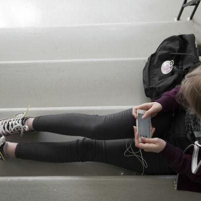 Nuori nainen katsoo kännykkää rappukäytävässä.