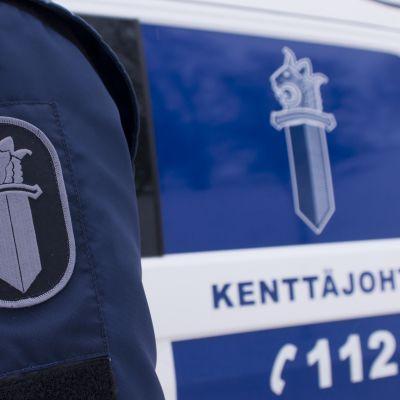 Poliisin hihamerkki ja poliisiauto