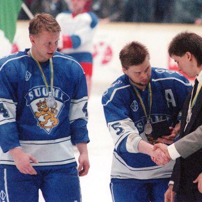 Leijonien kapteeni Timo Jutila ja päävalmentaja Pentti Matikainen kättelevät hopeamitalit kaulassa.
