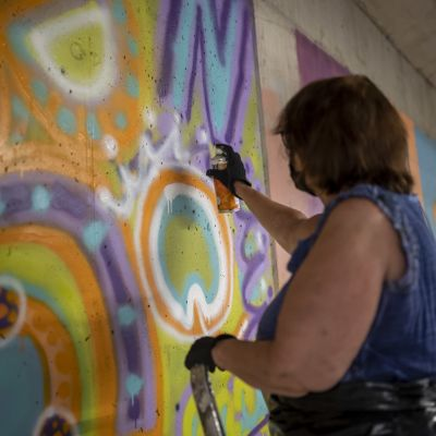 Nainen maalaamassa graffitia spraymaalilla.