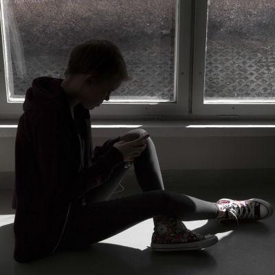Nuori nainen katsoo kännykkäänsä ikkunalaudalla.