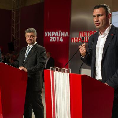 Petro Porosjenko och Vitalij Klytjko talar vid en presskonferens under valdagen den 25 maj 2014.