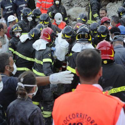 Räddningsarbetare söker igenom rasmassor i Pescara del tronto