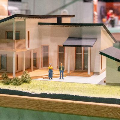 En miniatyrmodell av ett bostadshus i en glasmonter