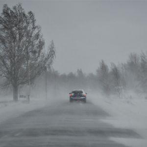 Bil på väg längs landsväg i snöyra och hård vind.