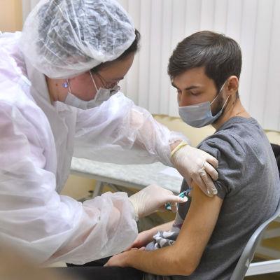 En man som får en injektion med vaccinet Sputnik V på en poliklinik i Moskva