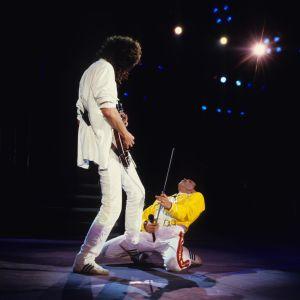 Queen live med Brian May stående och Freddie Mercury på knä spelande luftgitarr på sitt kapade mikrofonstativ.  Wembley 1986.